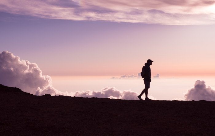silhouette of man walking under the sky
