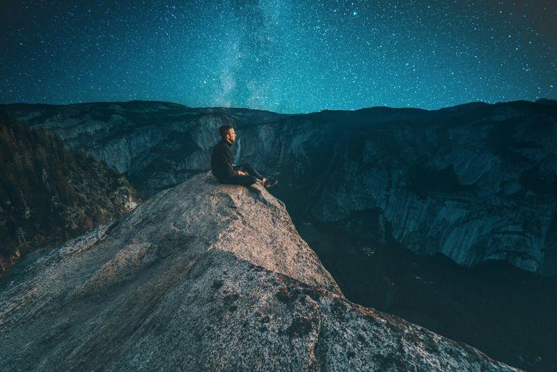 a man sitting under stars