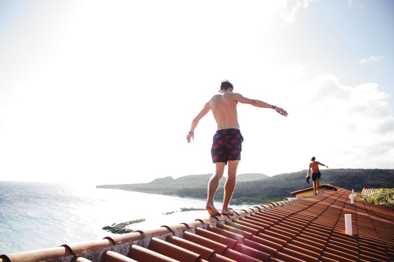 man waling on house roof